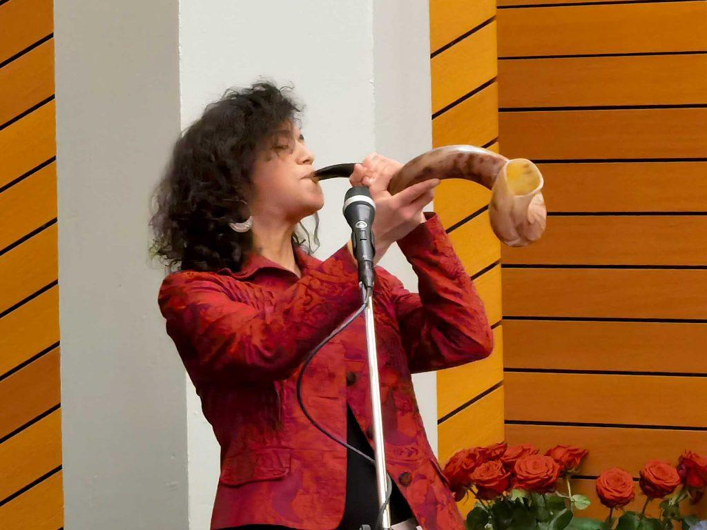 Frau blaest in Horn